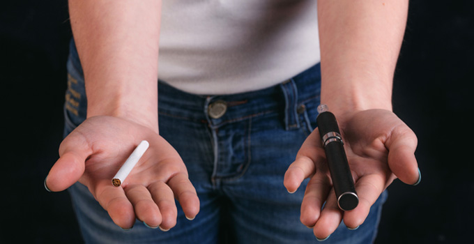 A person holds a cigarette in one hand and an electronic cigarette in the other.